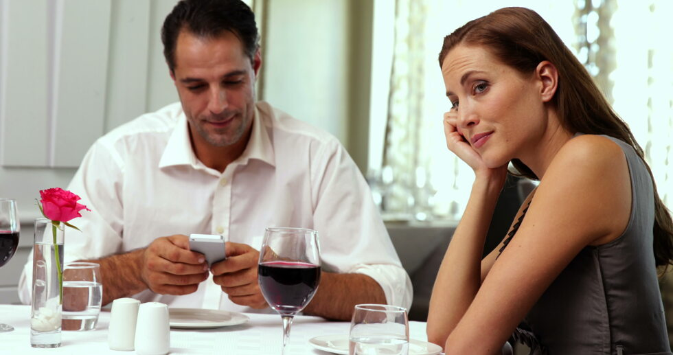 stock-footage-bored-woman-waiting-for-her-date-to-stop-texting-at-a-restaurant