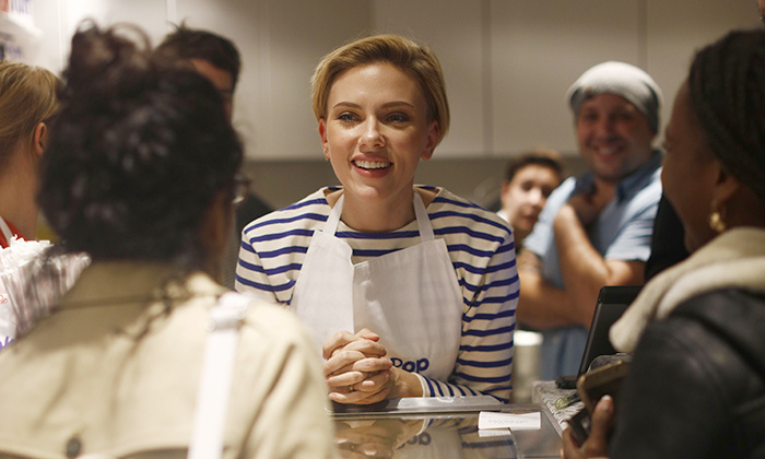US actress Scarlett Johansson speaks to a customer at the opening of the Yummy Pop gourmet popcorn shop in the Marais district of Paris on October 22, 2016. The concept is a labour of love with her French husband, advertising executive Romain Dauriac. And the couple hope that if their 'Real Vermont Cheddar' and other savoury and sweet recipes are a hit, they will open other shops elsewhere.